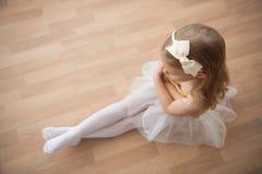 Recht sorgfältiges Ballettmädchen, das im weißen Ballettröckchen an Tanz studi sitzt Lizenzfreies Stockbild