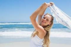 Recht sorglose blonde Aufstellung auf dem Strand mit Schal Stockbild
