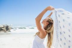 Recht sorglose blonde Aufstellung auf dem Strand mit Schal Stockfoto