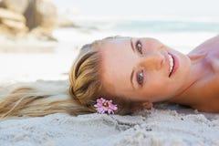 Recht sorgloses blondes Lügen auf dem Strand Stockfoto