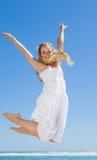 Recht sorgloses blondes Springen und Lächeln an der Kamera auf dem Strand Stockfoto