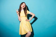 Recht spielerisches Mädchen im Kleid, das das Friedensgeste und -c$blinzeln zeigt Lizenzfreies Stockbild