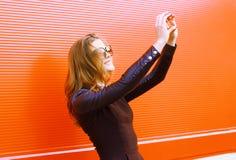 Recht stilvolle Frau macht Selbstporträt auf dem Smartphone Stockbild