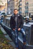 Recht stilvoller Kerl lehnt sich auf einem Boot in der Herbstzeit London Lizenzfreie Stockfotografie