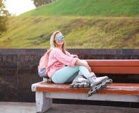 Recht stilvolles lächelndes Rollenmädchen auf der Bank im Stadtpark Lizenzfreies Stockbild