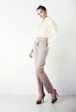 Recht stilvolles Mädchen in der weißen Hose und in der Bluse lizenzfreie stockbilder