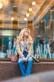 Recht träumerische Frau, die auf jemand beim Sitzen auf Shopschwelle am warmen Herbsttag, reizend blonde weibliche Aufstellung ge Stockbilder