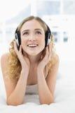 Recht vergnügtes blondes Lügen im Bett, das Musik hört Stockfotos