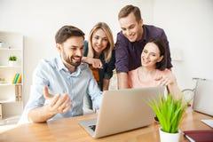 Recht vier Büroangestellte besprechen ein Projekt lizenzfreie stockbilder