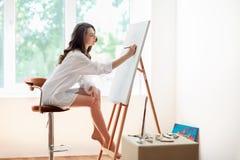 Recht weibliche Künstlermalereigrafik am Studio stockfotografie
