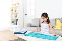 Recht weibliche Kleinkindkinder, die Kleidung falten lizenzfreie stockbilder