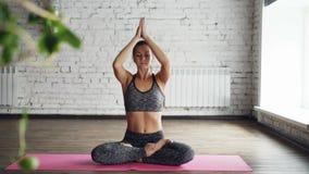 Recht weiblicher Yogalehrer demonstriert Körpertorsionen in Lotussitz, dehnt aus und tut das dann entspannende namaste stock video