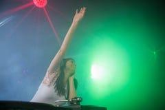 Recht weibliches DJ, das ihre Hand beim Spielen von Musik wellenartig bewegt Stockfotografie