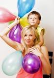 Recht wirkliche Familie mit Farbe steigt auf weißem Hintergrund, blon im Ballon auf Stockfoto