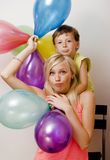 Recht wirkliche Familie mit Farbe steigt auf weißem Hintergrund, blonde Frau mit kleinem Jungen am hellen Lächeln der Geburtstags Stockbilder