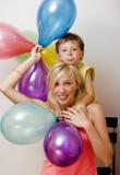 Recht wirkliche Familie mit Farbe steigt auf weißem Hintergrund, blonde Frau mit kleinem Jungen am hellen Lächeln der Geburtstags Lizenzfreies Stockbild