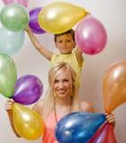 Recht wirkliche Familie mit Farbe steigt auf weißem Hintergrund, blonde Frau mit kleinem Jungen am hellen Lächeln der Geburtstags Stockfoto