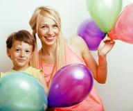 Recht wirkliche Familie mit Farbe steigt auf weißem Hintergrund, blonde Mutter mit nettem Sohn auf Geburtstagsfeierfeier im Ballo Lizenzfreies Stockbild