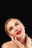 Recht zarte Frau berühren ihr Gesicht auf schwarzem Hintergrund stockfoto