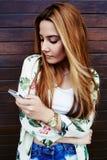 Recht zufällig-gekleideter weiblicher Lesetext beim Halten ihres intelligenten Telefons stockfotografie