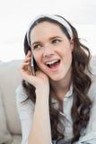 Recht zufällige Frau, die am Telefon erstaunt wird Lizenzfreie Stockfotografie