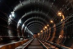 Rechte cirkelmetrotunnel met buizenstelsel en twee verschillende lichten: wit en geel Royalty-vrije Stock Foto