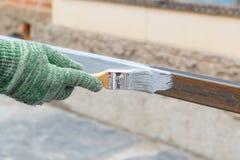 Rechte Hand im Lappenhandschuh-Pinselstahlpfosten in der grauen Antirostfarbe Stockfoto