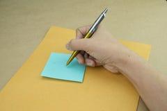 Rechte Hand schreiben auf Post-It Stockfoto