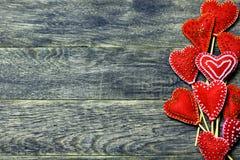 Rechte Rahmengrenze von handgemachten Herzen des Filzes rote Farbauf dunklem altem hölzernem Hintergrund Stockbilder