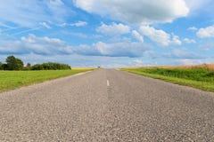 Rechte weg die zich voorbij de horizon tot blauwe hemel met overladen wolken uitbreiden royalty-vrije stock foto