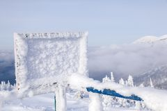 Rechteckige hölzerne Platte bedeckt mit Reif auf Skiort AG lizenzfreie stockfotos