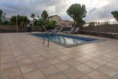 Rechteckiger Swimmingpool mit gepflasterten Einfassungen stockfoto