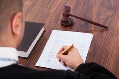 Rechter die document in rechtszaal ondertekenen Royalty-vrije Stock Fotografie