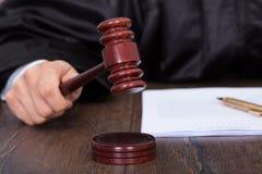 Rechter die oordeel geven door houten hamer te raken stock afbeelding