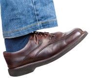 Rechter Fuß in den Jeans und im braunen Schuh unternimmt einen Schritt Stockbilder