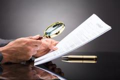 Rechter Looking At Document met Vergrootglas royalty-vrije stock foto's