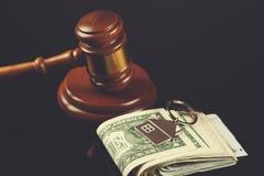 Rechter met huissleutel en geld stock afbeelding