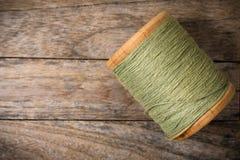 Rechterkant van het spoel de groene garen op hout Stock Afbeelding