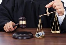 Rechters opvallende hamer terwijl het houden van schaal met geld Stock Fotografie