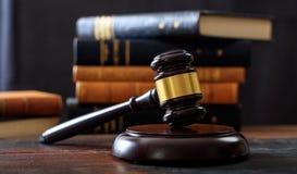 Rechtershamer op een houten bureau, de achtergrond van wetsboeken