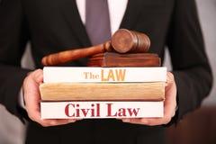 Rechtsanwalt, der Bücher und Gerichtshammer hält Lizenzfreie Stockfotografie