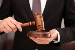 Rechtsanwalt, der Gerichtshammer hält Stockbild