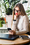 Rechtsanwalt - junger asiatischer Frauenrechtsanwalt, der bewegliches smartphone betrachtet und Kaffee vom wegwerfbaren Papiercup Stockbild