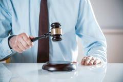 Rechtsanwalt oder Auktionator, die seinen Hammer anheben stockbilder