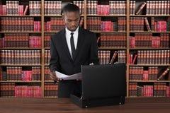 Rechtsanwalt-With Papers And-Aktenkoffer am Schreibtisch stockbild