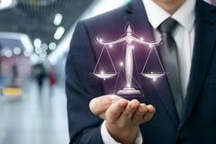 Rechtsanwalt zeigt die Skalen von Gerechtigkeit in der Hand stockfotografie