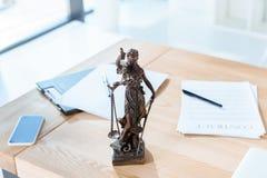 Rechtsanwaltarbeitsplatz mit themis Skulptur lizenzfreie stockbilder