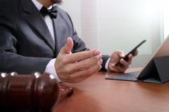 Rechtvaardigheid en wetsconcept Mannelijke advocaat in het bureau met messingsschaal op houten met slimme telefoon royalty-vrije stock foto's