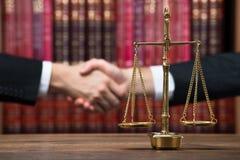 Rechtvaardigheid Scale On Table met de Handen van Rechtersand client shaking stock foto