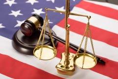 Rechtvaardigheidsschaal en houten hamer op de vlag van de V.S. Stock Foto